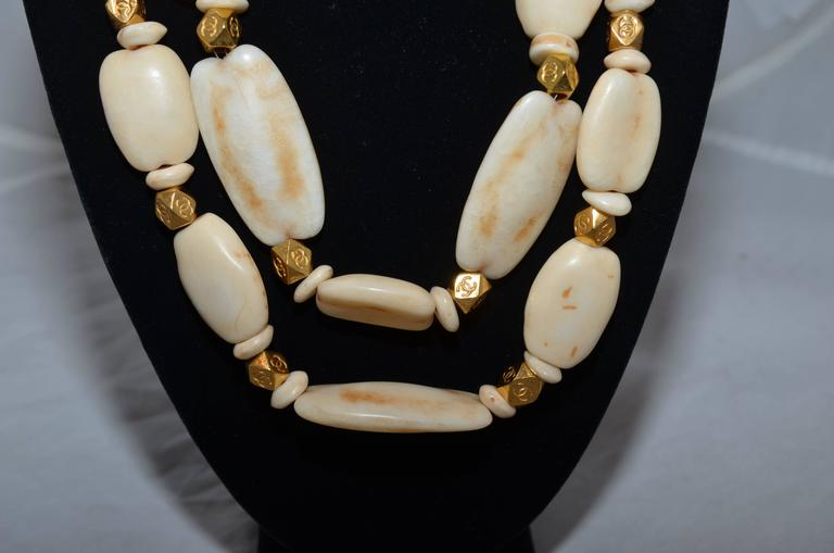 Chanel necklace from 1996 Spring collection with a double strand of chunky faux ivory beads and CC engraved gold-tone spacers. Necklace has a chain-link and hook closure for sizing. Made in France.