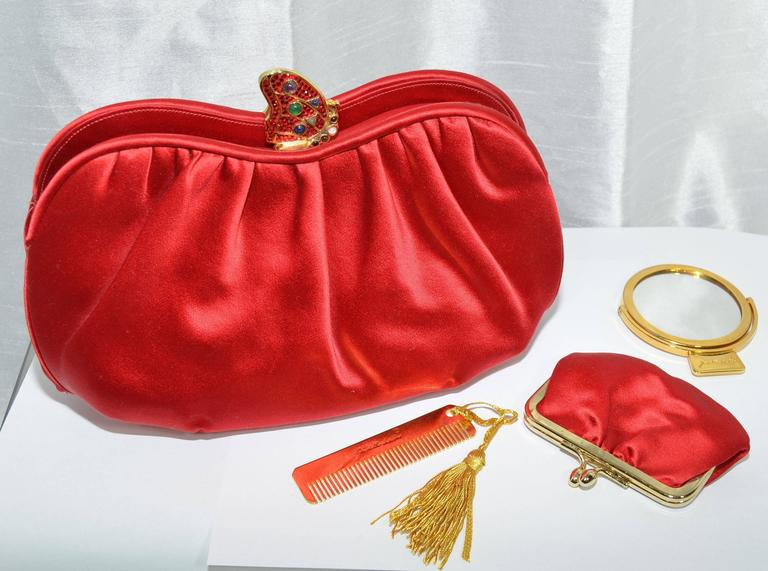 Gorgeous Judith Leiber clutch featured in a blue red satin fabric with a slightly ruched opening. There are three separate compartments with the center compartment including one zipper pocket and one slip pocket, with a gold-tone jeweled metal