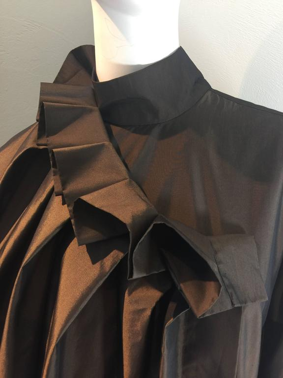 Issey Miyake vintage 1980's silk and poly blend lightweight tafetta gown in a tobacco brown. Unstructured shape to the body of the gown with volume created with chunky box pleats across the back. Flowing front with side pockets. Box pleated neck