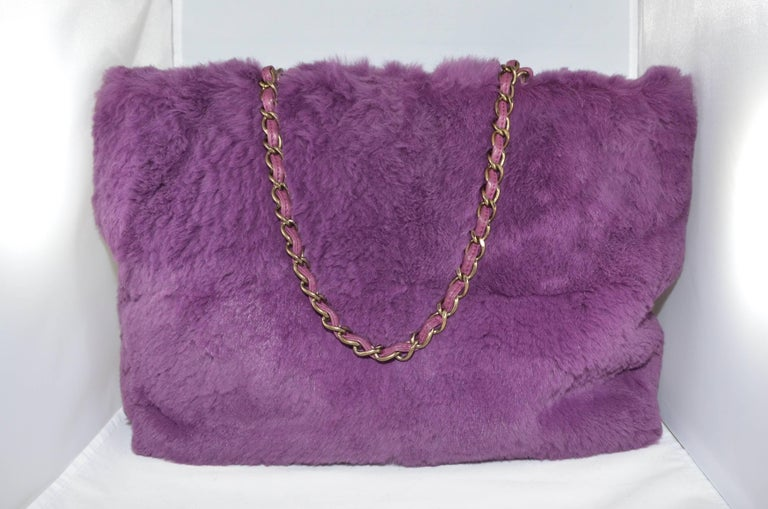 Chanel soft and plush purple cuddle bag in luxuriously soft lapin fur, leather lining, with classic chain handles and CC logo on the front. Dated from 2000-2002. Shoulder tote features two interior zippered pockets and a double shoulder strap.