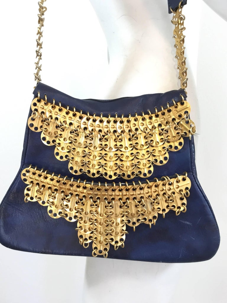 1960's production RICAF Paco Rabanne bag featured in blue leather with gold disks. Bag has two separate compartments and a flat leather shoulder handle attached by gold disks. Bag shows some wears to the leather with spots of discoloration and