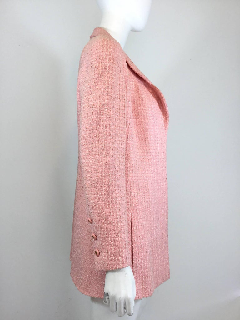 Chanel jacket featured in a pink tweed with an open front and pockets at the hip. Jacket has signature logo buttons on the cuffs, fully lined and also has a chain trim along the inside of the hem. Excellent condition.  Bust 38'', sleeves 24'', waist