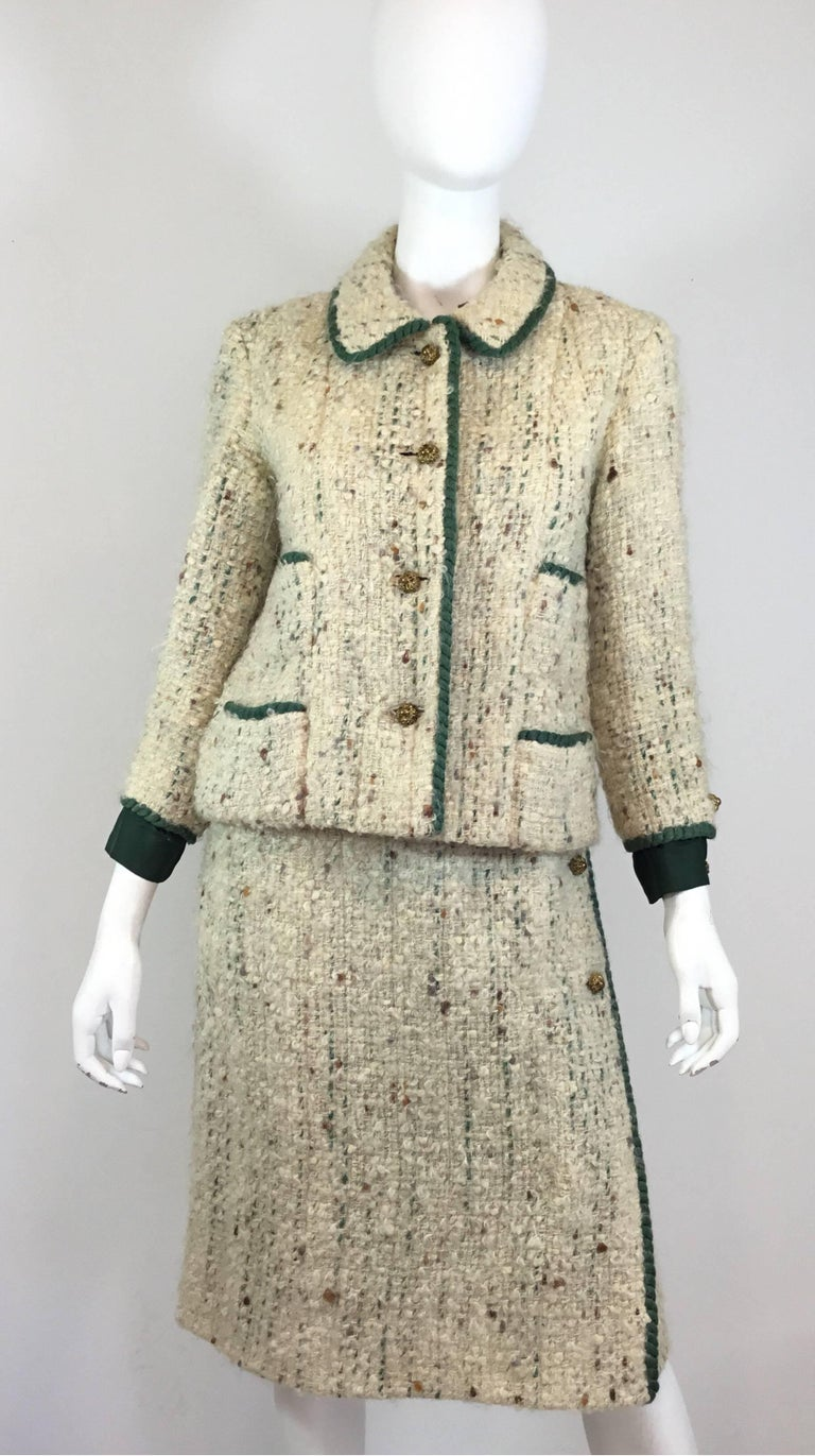 Chanel Couture skirt suit, circa 1950-1960's. Tweed jacket is featured in an off white tweed knit with a green trim, antique brass hardware button closures, total of four patch pockets, silk cuff and button detail at the sleeves, chain trim along to