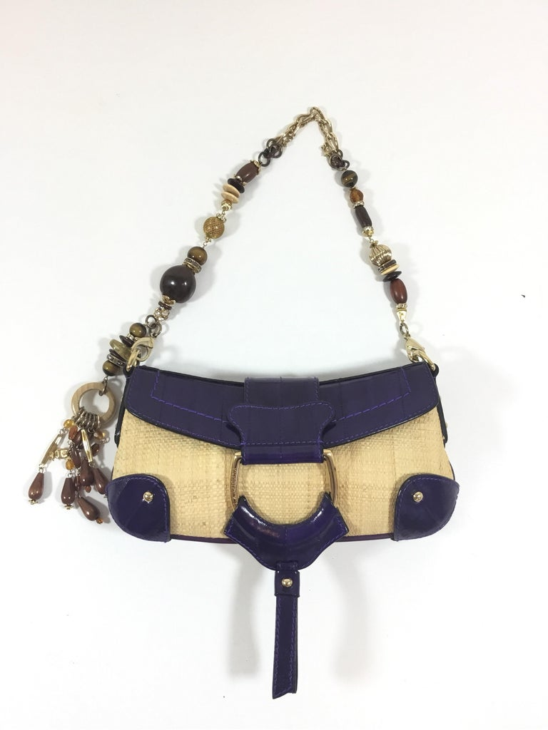 Dolce & Gabbana purse featured in straw and eel skin in purple with a bead and jewel gold chain handle, handle has clips at each end for easy removal, flap and snap stud closure. Interior is fully lined in a jacquard fabric with one slip pocket.