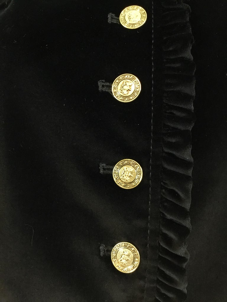 """Dolce & Gabbana velvet jacket in black with gold tone button fastenings and a ruffled trim. Jacket has a total of 3 buttoned pockets that have not been cut for use. Fully lined in signature leopard print. Made in Italy, size 44.  Bust 36"""", sleeves"""