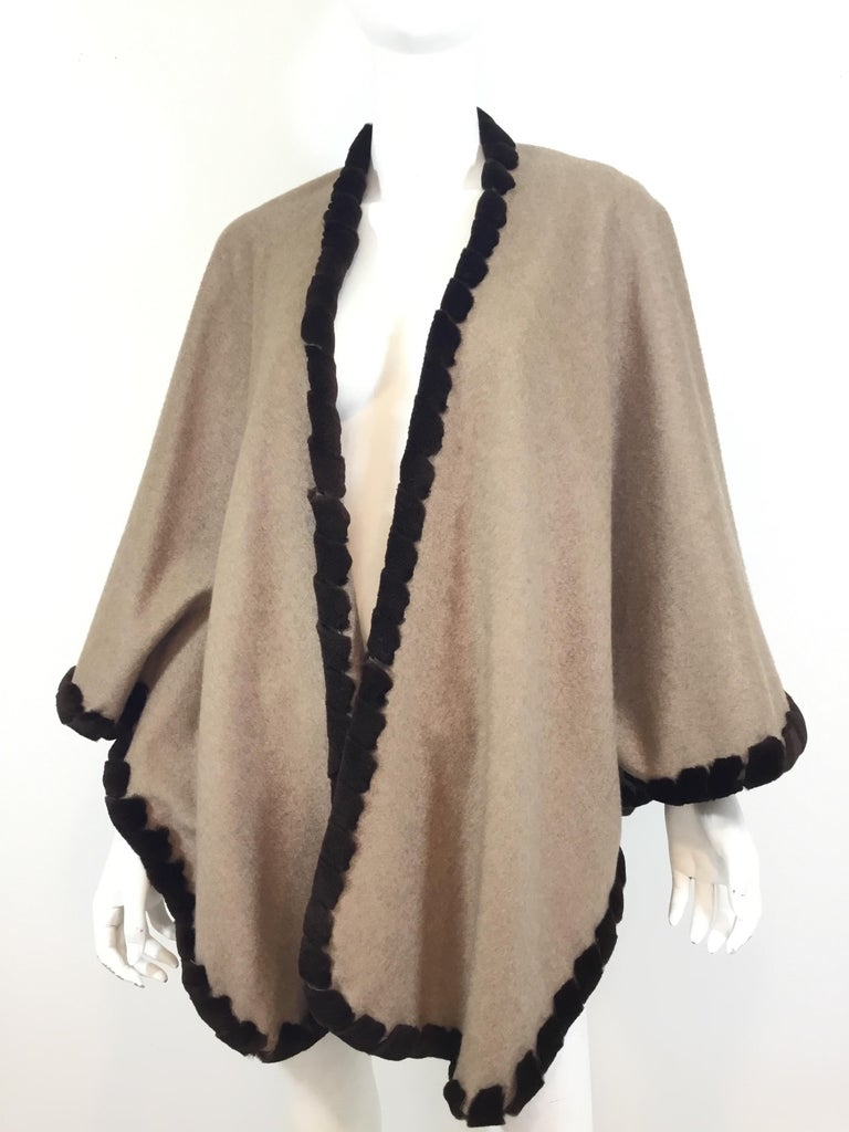 """Loro Piana cashmere cape featured in a taupe color with a brown sheared mink trim. Optional buttons to create an insert for arms. Estimated retail $10k. Made in Italy. 100% cashmere.   Bust (laying flat) 38"""" across, length 30"""""""