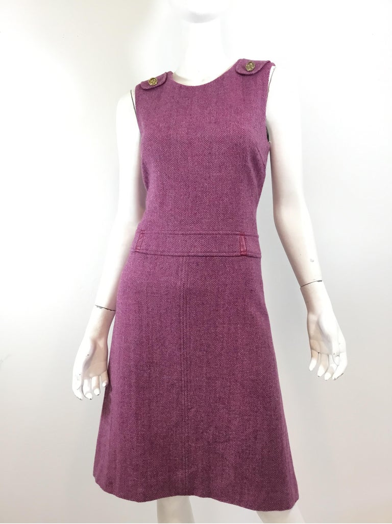 Chanel Tweed Dress featured in purple with gold tone CC buttons at the shoulders, subtle leather detail at the waistline, back zipper fastening, and full lining.  Bust 32'' Waist 30'' Hips 34'' Length 39''