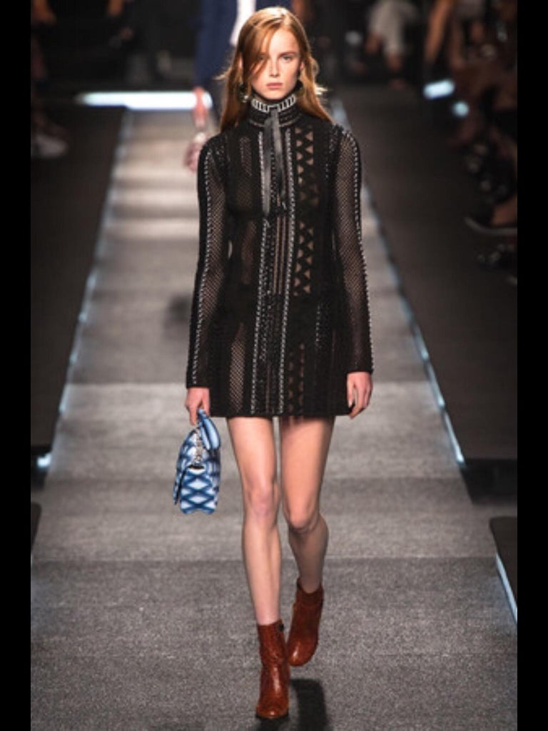 Black Louis Vuitton dress features an open/cutout fitting knit fabric with a black and beige leather trim around the neck. Slip on entry with a silver-tone LV engraved hook-and-eye fastening at the back. Dress includes nude slip shell. Labeled size