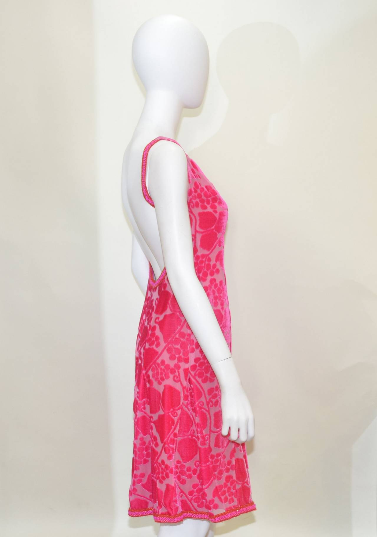 Chanel dress features a bias cut floral velvet pattern throughout with braid trim. Plunging open back; fit and flare skirt, back zipper,hook-and-eye fastening and 100% silk lining. Made in France. 33% nylon, 33% acrylic, 16% wool, 13% cotton, and 5%