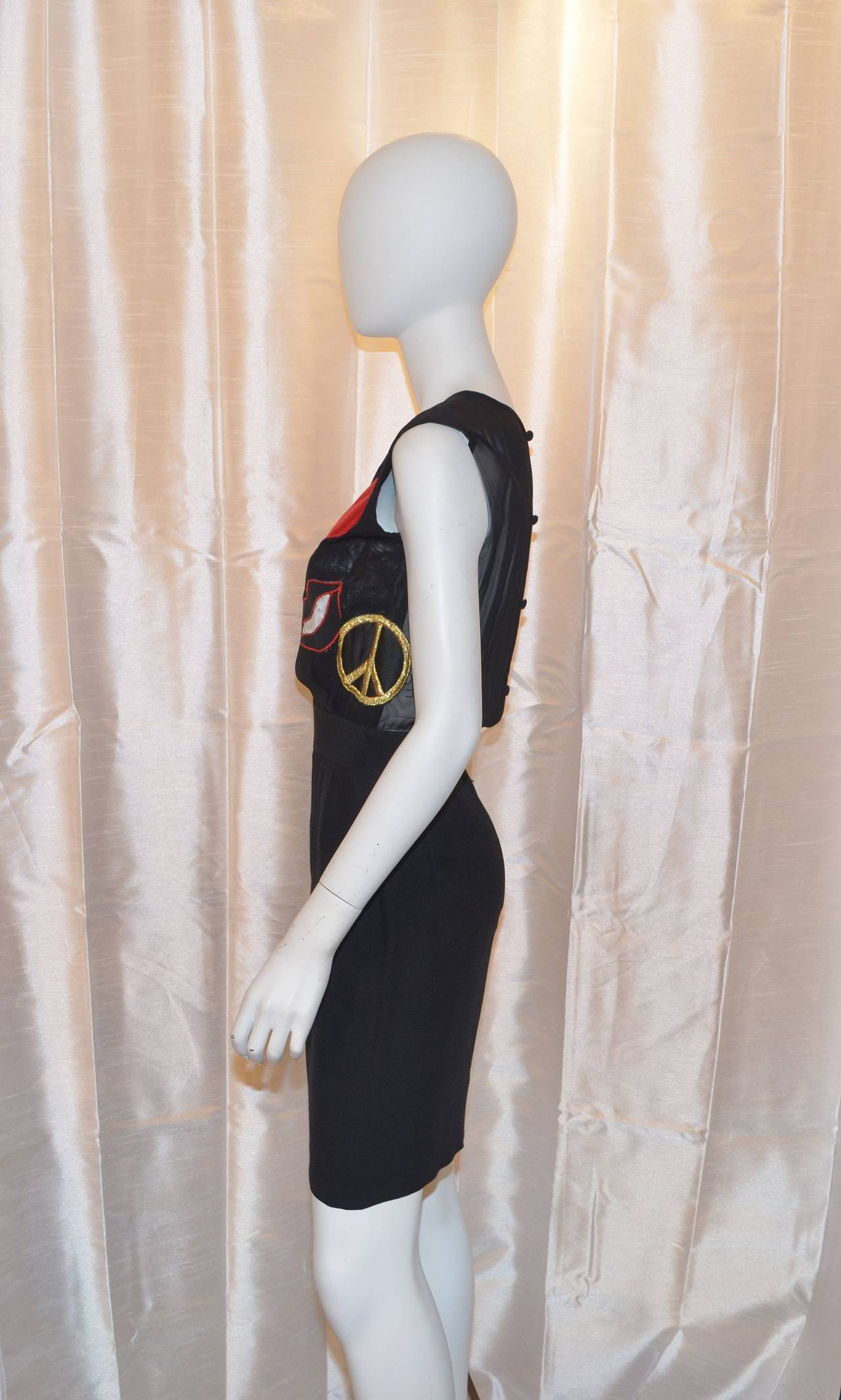 Moschino dress features some fun patches over the bust area, back zipper fastening, and button closures. Made in Italy, size 40 (US size 6).  Measurements: Bust - 34'' Waist - 26'' Hips - 36'' Length - 37''