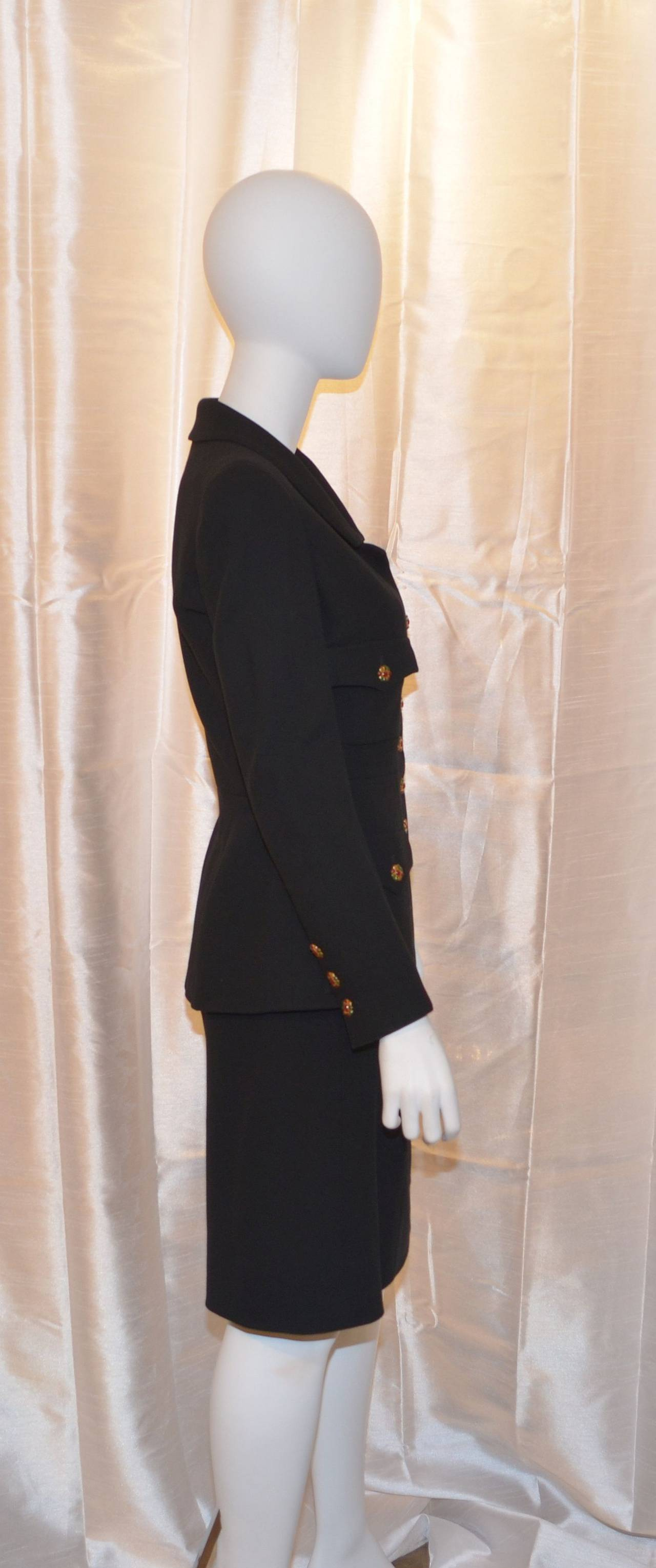 Chanel suit jacket features beautiful gripoix glass button closures along the front center as well as on the flap pockets and cuffs. Skirt has a back zipper and hook-and-eye closure. Made in France, size 40. Suit is made with 100% wool and lined
