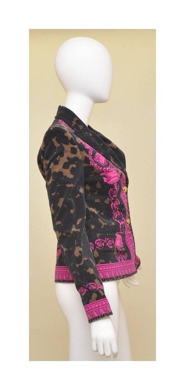 Versace Jacket is an Italian size 42, US 8. Features black, brown, and fuchsia velvet, gold-tone Medusa head button closures, Medusa print throughout, and two front flap pockets. Jacket is fully lined and in EXCELLENT condition!