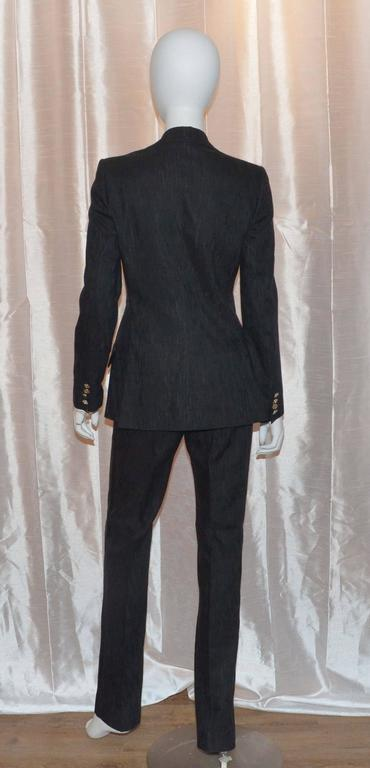 Dolce & Gabbana ensemble features a unique subtle jaquard pattern to the silk blend fabric throughout. Jacket has a satin collar, gold and silver-tone button closures along the front and on the cuffs, and two flap pockets at the hem. Pants have a