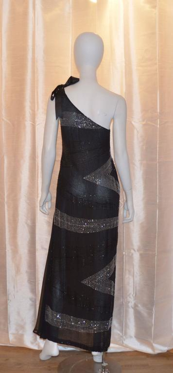 Alfred Fiandaca mid 1990's bias cut gown features black and silver beading throughout, elegant one-shoulder style with a ribbon tie, side zipper and hook-and-eye closure, and a train on the left side of the hem.  Very light weight. Photo ad of gown