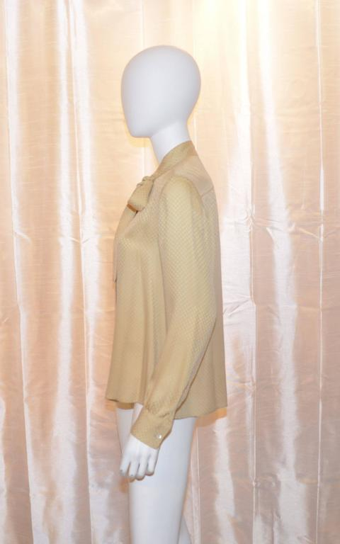 Chanel blouse has button closures along the front and neck tie detail. Fine CC logo print throughout. There are button closures at the cuffs as well. Made in France. Great condition with no flaws to mention.  Measurements: Bust - 42'' Sleeves -