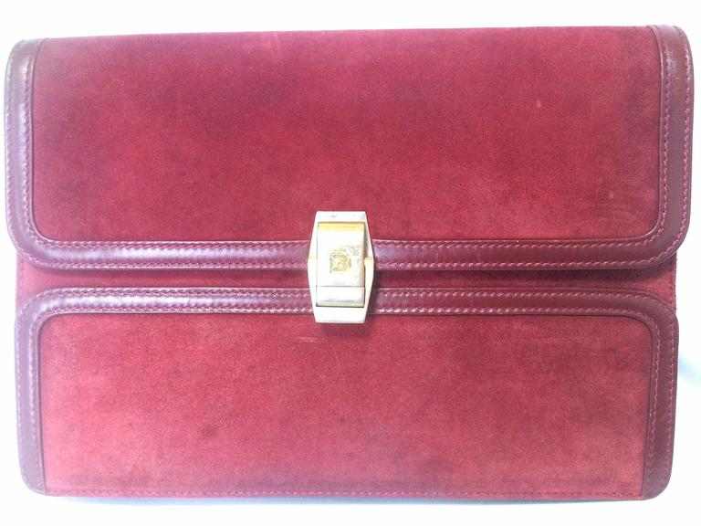 1980s. Vintage BALLY genuine wine suede leather clutch bag, mini purse with gold tone logo motif.