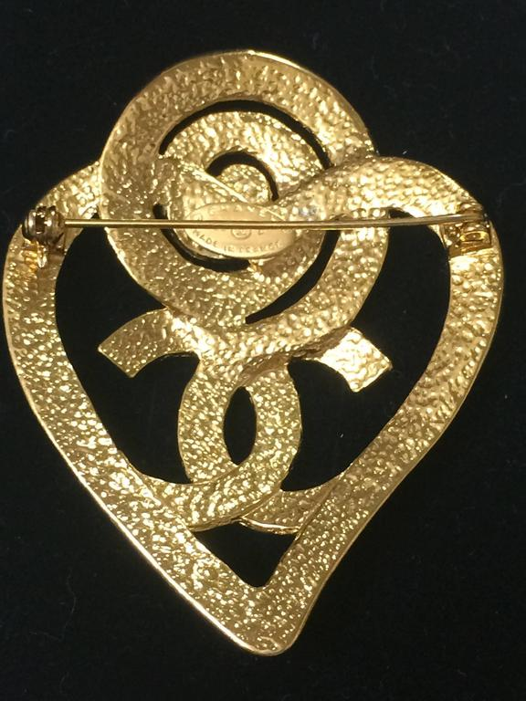 Women's Vintage CHANEL gold tone heart and snail design brooch with CC mark at center. For Sale