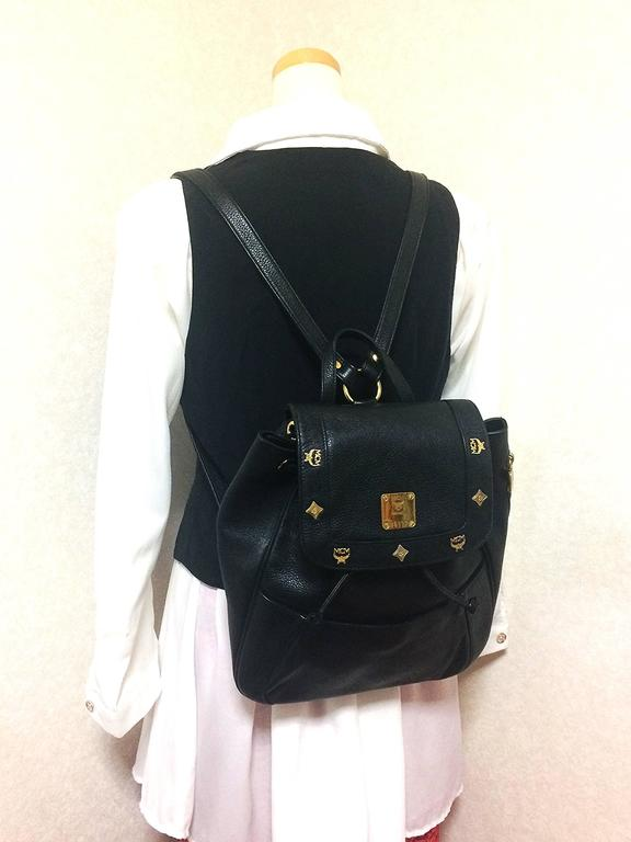 1980s. vintage MCM genuine leather black backpack with gold tone hardware and charms. Designed by Michael Cromer. Unisex bag for daily use.  MCM has now come back in trend and so hot in the market!!  This is the vintage MCM black genuine leather