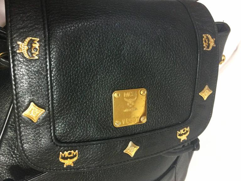 80's vintage MCM genuine leather black backpack with golden logo motifs. Unisex For Sale 1