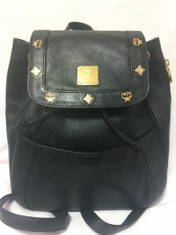 Black 80's vintage MCM genuine leather black backpack with golden logo motifs. Unisex For Sale
