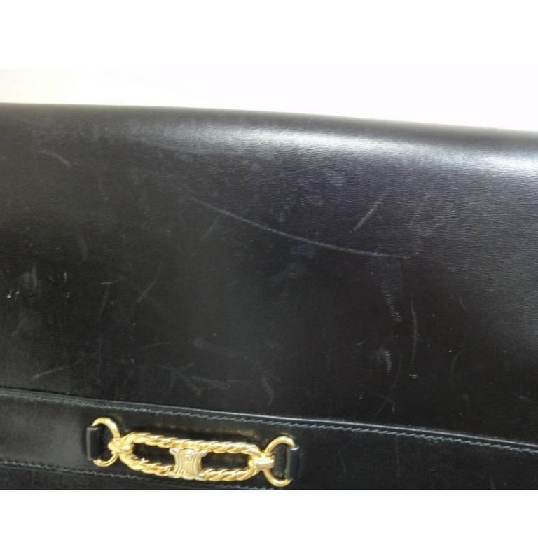 Vintage Celine black calfskin leather clutch bag with iconic golden logo motif. 3