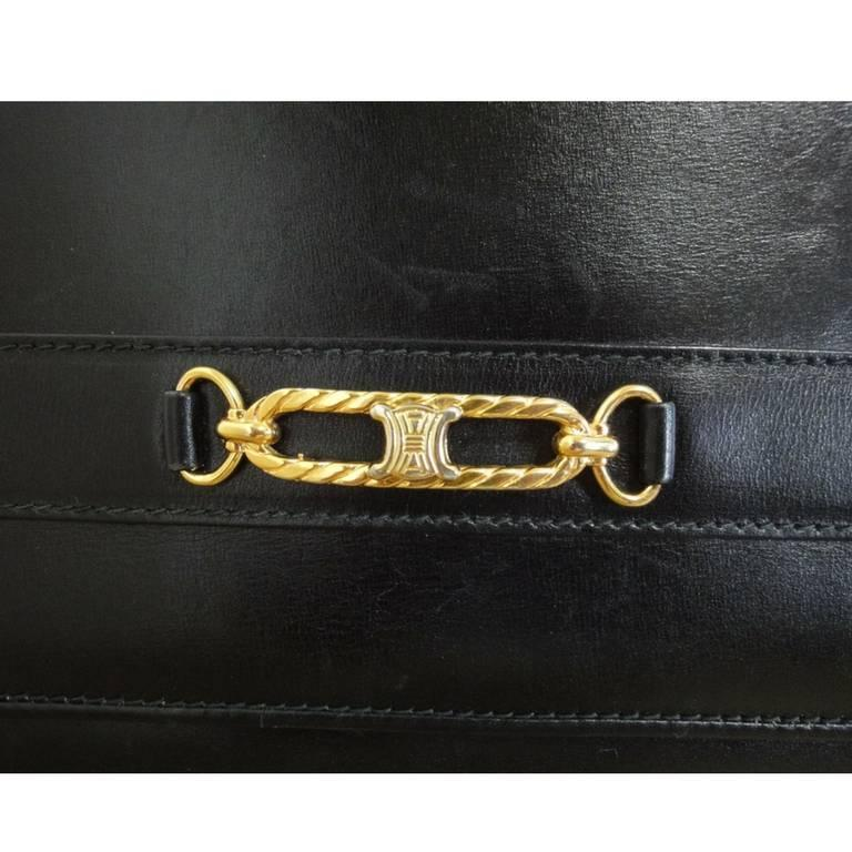 Vintage Celine black calfskin leather clutch bag with iconic golden logo motif. 2