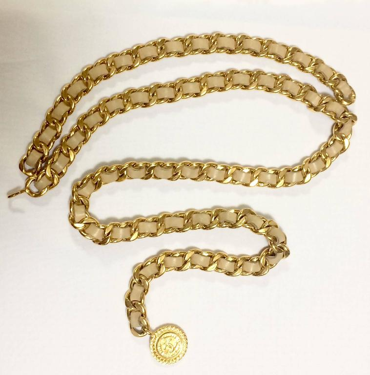Beige Vintage CHANEL beige leather chain belt with golden CC and mademoiselle charm. For Sale