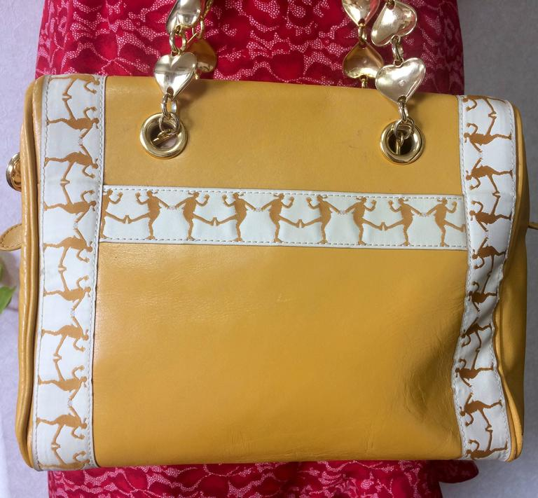 Yellow Vintage MOSCHINO yellow handbag with golden heart chains and dancing girl motif. For Sale