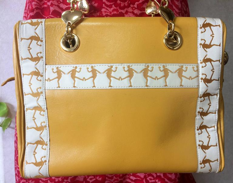 Women's Vintage MOSCHINO yellow handbag with golden heart chains and dancing girl motif. For Sale