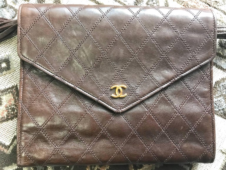 1980s. Vintage CHANEL brown goatskin clutch bag, large wallet, bill, checkbook, iPhone purse with a tassel and golden mini CC motif. Unisex use.  Introducing a CHANEL vintage functional wallet in dark brown goatskin from the 80s. Wallet, iPhone