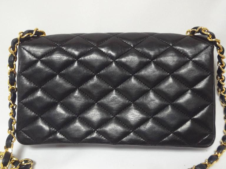 MINT. 80's vintage CHANEL black lambskin chain shoulder bag with golden large CC closure and beak flap tip. Classic 2.55 bag.