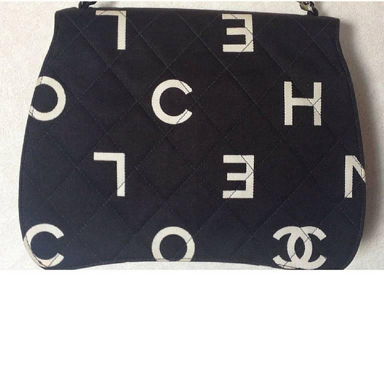 Vintage CHANEL black fabric canvas chain handbag with white Chanel cc logo print all over. Very unique shape.