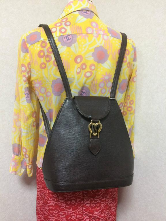 1990s Vintage MOSCHINO genuine dark brown leather backpack with golden and black M logo motif from cheap and chic by moschino. Perfect daily bag.