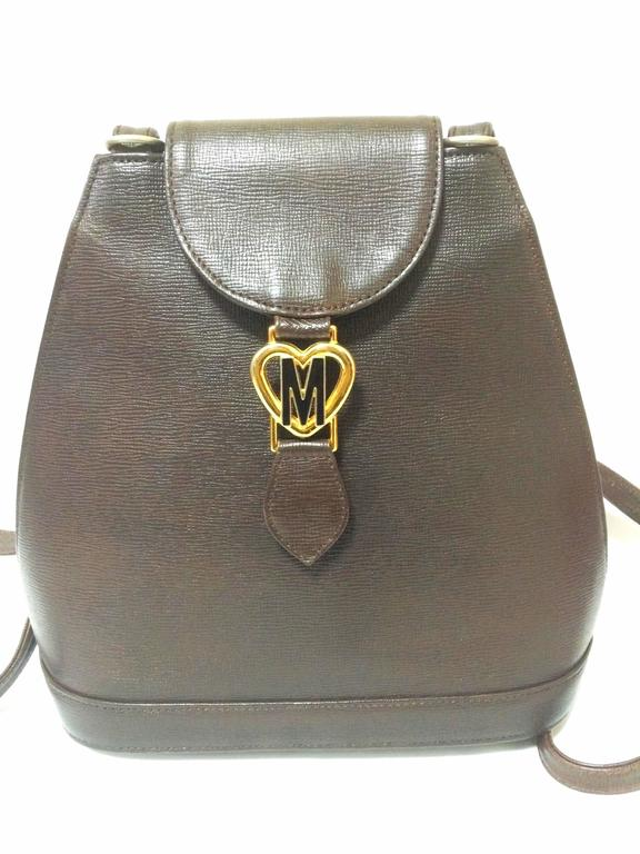 Black Vintage MOSCHINO dark brown leather backpack with golden and black M logo. For Sale