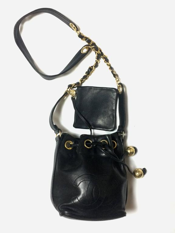 1990s. Vintage CHANEL black lamb leather mini hobo bucket drawstring shoulder bag with golden ball charms and CC stitch mark. Classic purse
