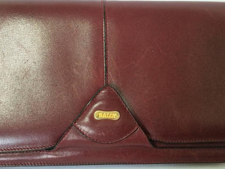 1980s. Vintage Bally wine leather clutch bag, party and classic purse with gold tone logo motif. Unisex use.