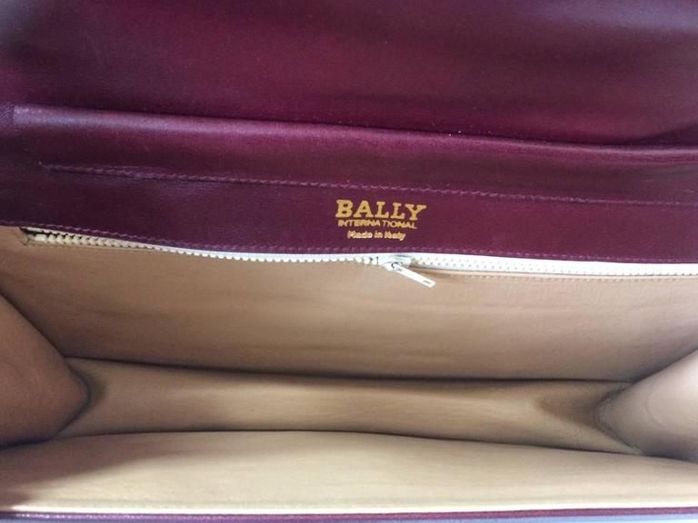 Women's or Men's Vintage Bally wine leather clutch bag, party and classic purse with golden logo. For Sale
