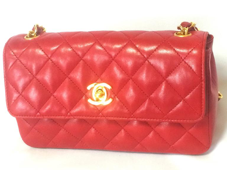 1990s. Vintage CHANEL classic mini flap 2.55 shoulder bag in lipstick red lambskin with golden CC and chain strap. Popular purse back in the era.  Here is another classic and one of the most popular purses from CHANEL....Vintage lambskin mini 2.55