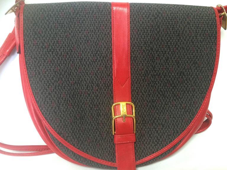 Brown Vintage Yves Saint Laurent oval navy shoulder bag with red shoulder straps. For Sale