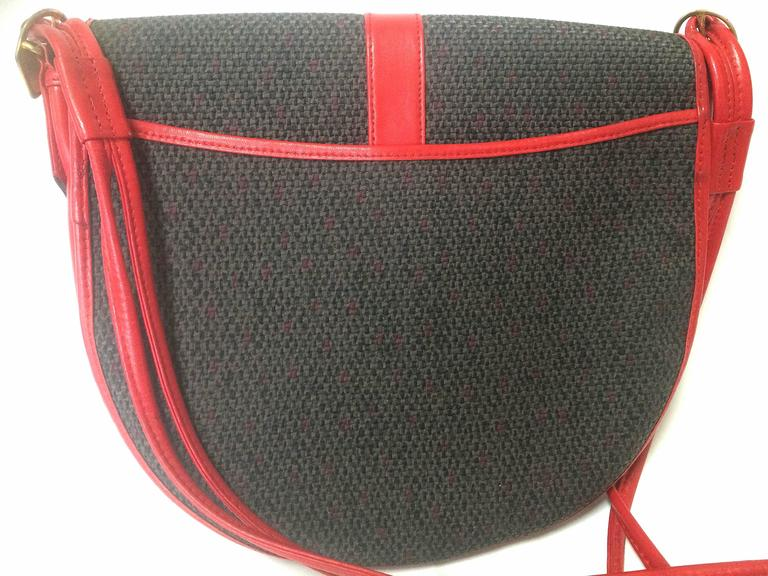 1990s. Vintage Yves Saint Laurent oval navy shoulder bag with red leather shoulder strap. Perfect daily use YSL purse.  Introducing another vintage piece from Yves Saint Laurent, shoulder bag with red leather trimmings and straps and the logo