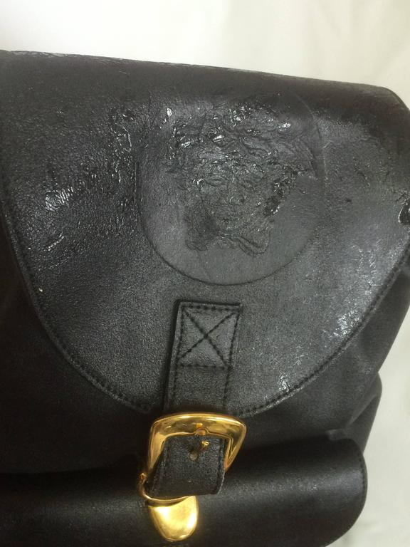 1990s. Vintage Gianni Versace black leather backpack with a big embossed medusa with gold tone hardware. Unisex bag for daily use.  This is the vintage GIANNI VERSACE black leather backpack that features a big medusa embossed at front flap and
