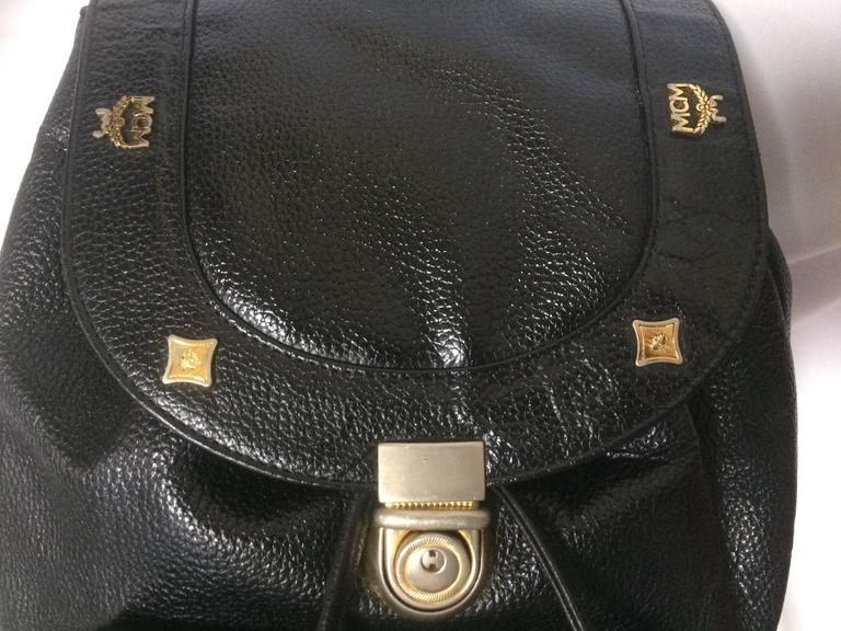 1980s. Vintage MCM genuine leather black backpack with golden studded logo motifs. Designed by Michael Cromer. Unisex bag for daily use.