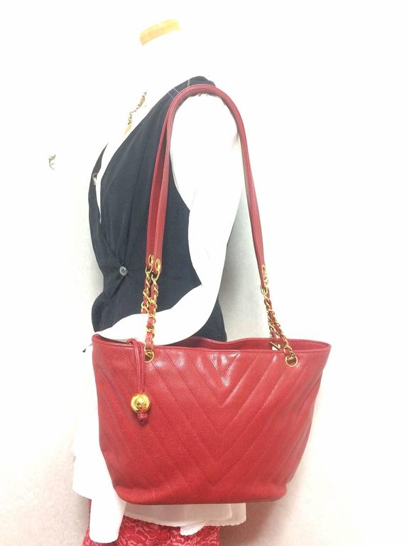 1990s. Vintage CHANEL red caviar leather v stitch, chevron style chain shoulder tote bag with golden CC ball charm. Classic purse for daily use.