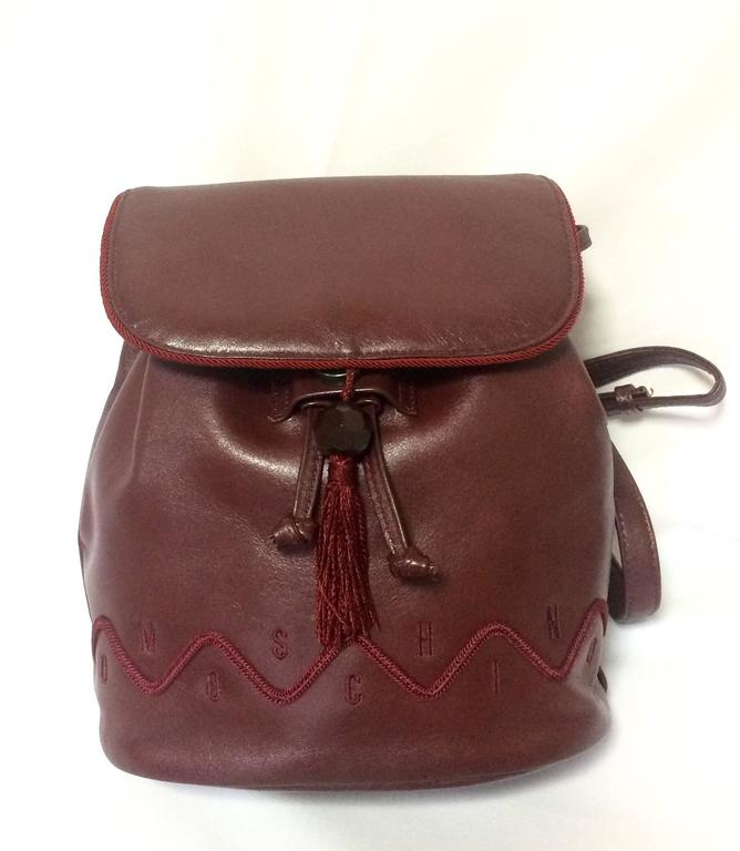 1990s. Vintage MOSCHINO genuine dark wine nappa leather backpack with tassel and logo embroidery motifs. Small to Medium size for daily use.  Introducing another unique and rare vintage piece from MOSCHINO back in the 90's. Small to medium size