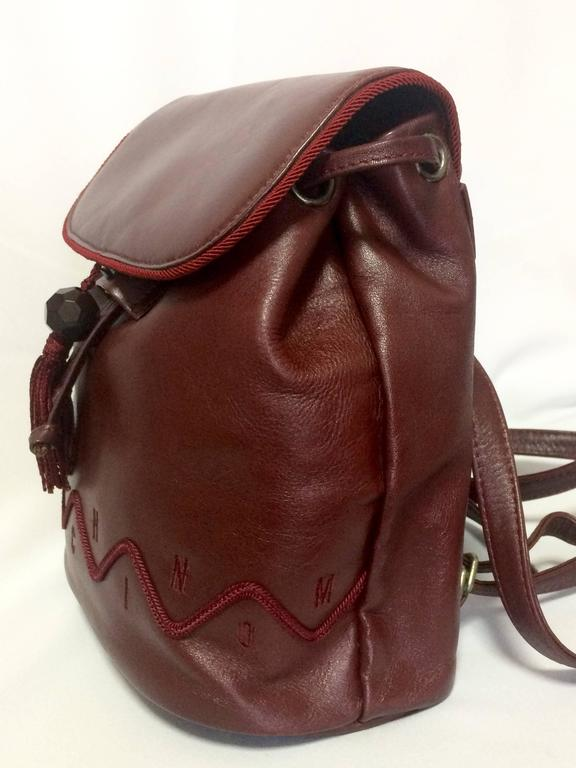 Women's Vintage MOSCHINO dark wine leather backpack with tassel and logo embroidery. For Sale