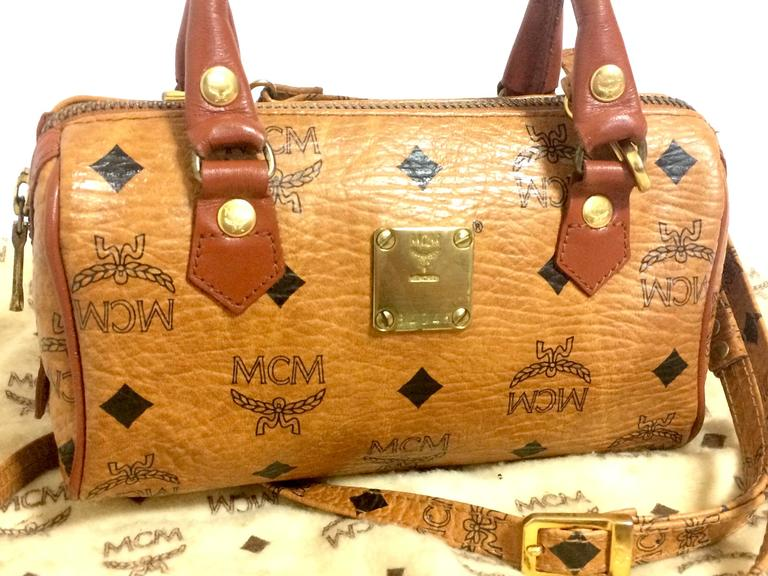1990s. Vintage MCM classic brown monogram mini speedy bag with shoulder strap. Must have purse, designed by Michael Cromer.  Here is another adorable vintage bag from MCM, designed by Michael Cromer, back in the 90's.  Mini speedy design handbag