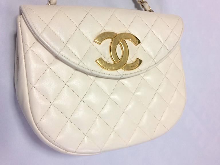 1980s. Vintage CHANEL ivory white lambskin 2.55 chain shoulder bag with large golden CC motif and oval flap.  Here is another rare piece, a hard-to-find vintage treasury bag from Chanel back in the 80's.  The unique thing about this purse is its