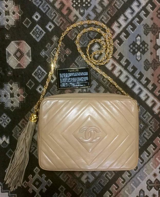 1990s. Vintage Chanel beige lamb leather 2.55 camera bag style chain shoulder bag with fringe and CC stitch mark. Chevron diamond shape stitches.  Introducing another fabulous vintage purse from CHANEL back in the early 90's.  Featuring unique