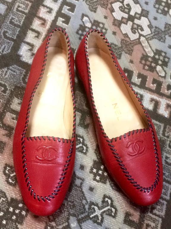 1990s. Vintage CHANEL lipstick red calfskin leather flat pump shoes with black stitches and CC mark. US 5.5-6.  This is a classic vintage flat shoes in beautiful red leather from CHANEL from the 90's.  Featuring black leather stitching decoration
