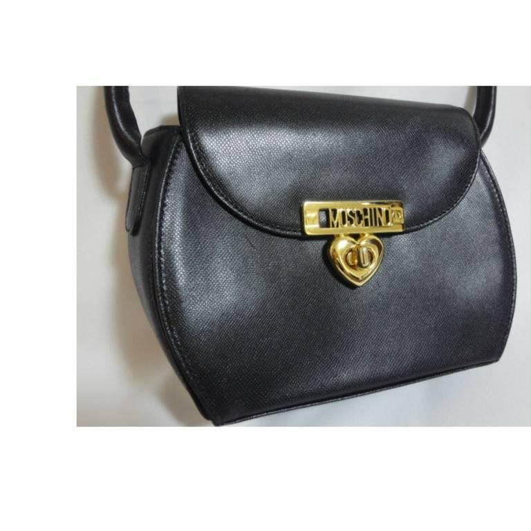 Vintage MOSCHINO black leather handbag, oval shape purse with golden logo motif. 2